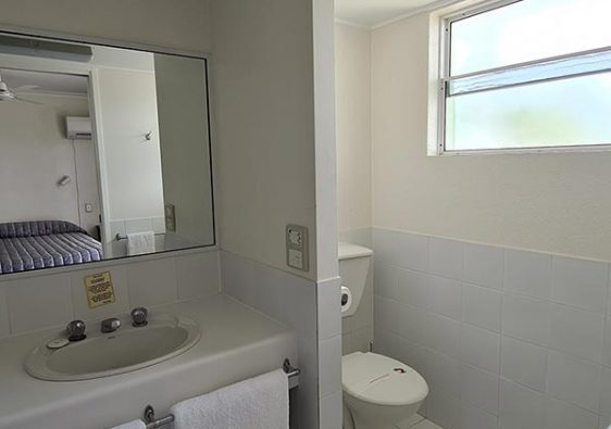 White bathroom with basin mirror and toilet and two white towels