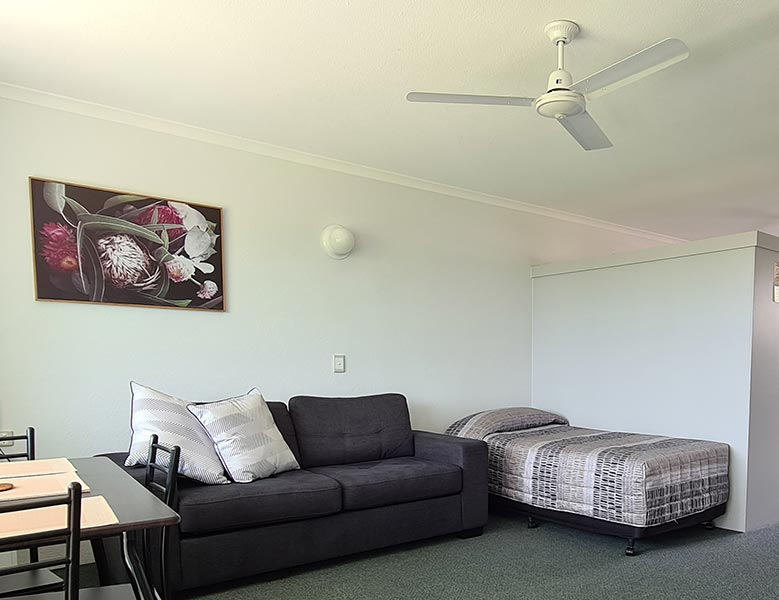 Family room with table and chairs, three seater couch and single bed