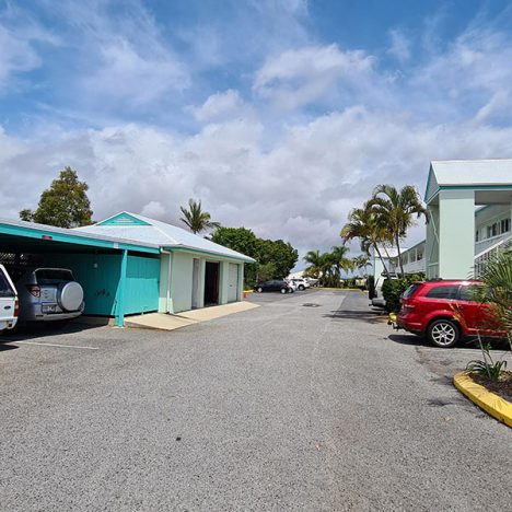 Large parking area of motel with a few cars parked