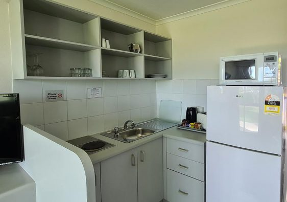 White Kitchenette with microwave, toaster, fridge and crockery on shelves