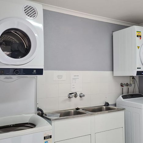 White and greay laundry with 2 washing machines, two dryers and twin basins