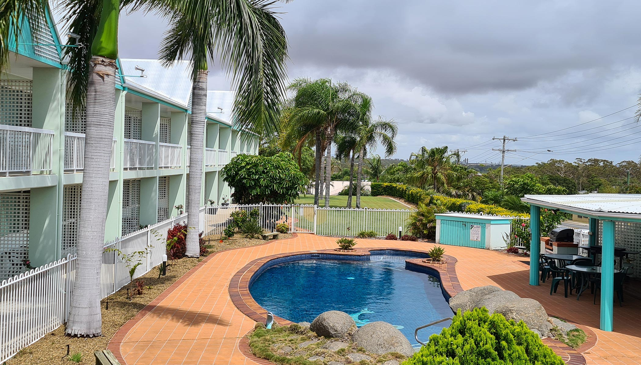 Elevated view of pool, BBQ area and double storey motel rooms with lush garden