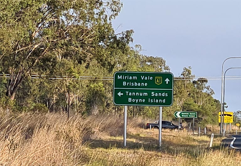 Green road sign on Bruce Highway pointing towards Tannum Sands and Boyne Island