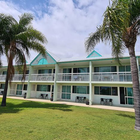 View of motel balconies with green grass and 3 palm trees