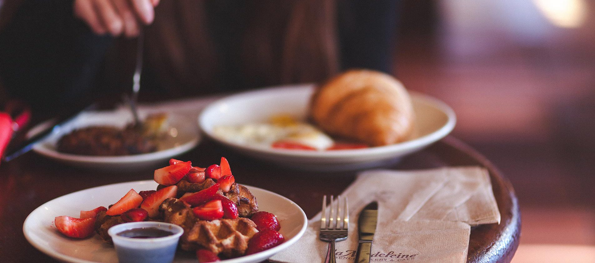 Table with berry waffle, croissant and blurred hand of someone using a fork