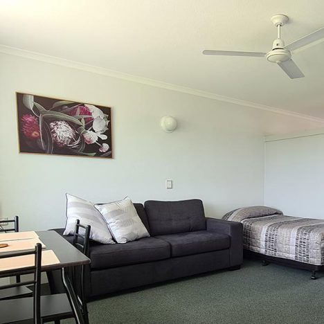 Family room with three seater couch and single bed and portrait